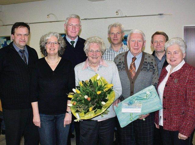 Foto: Kerstin Wessel Ferdinand Mönning und seine Frau freuen sich im Kreis des Vorstands im Kreis des Vorstands über Blumen und ein Präsent der Heimatfreunde Bad Westernkotten.